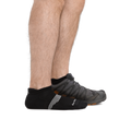 Man standing barefoot wearing Element No Show Tab Lightweight Athletic Socks with Cushion in Black and back foot also wearing an athletic sneaker