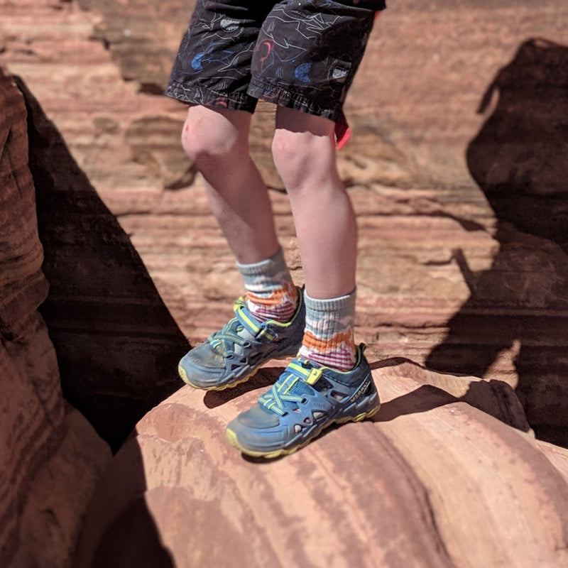 Kid standing on a rocky ledge, wearing hiking shoes and shorts wearing Three Peaks Micro Crew Hiking Sock in Glacier, Lifestyle Image