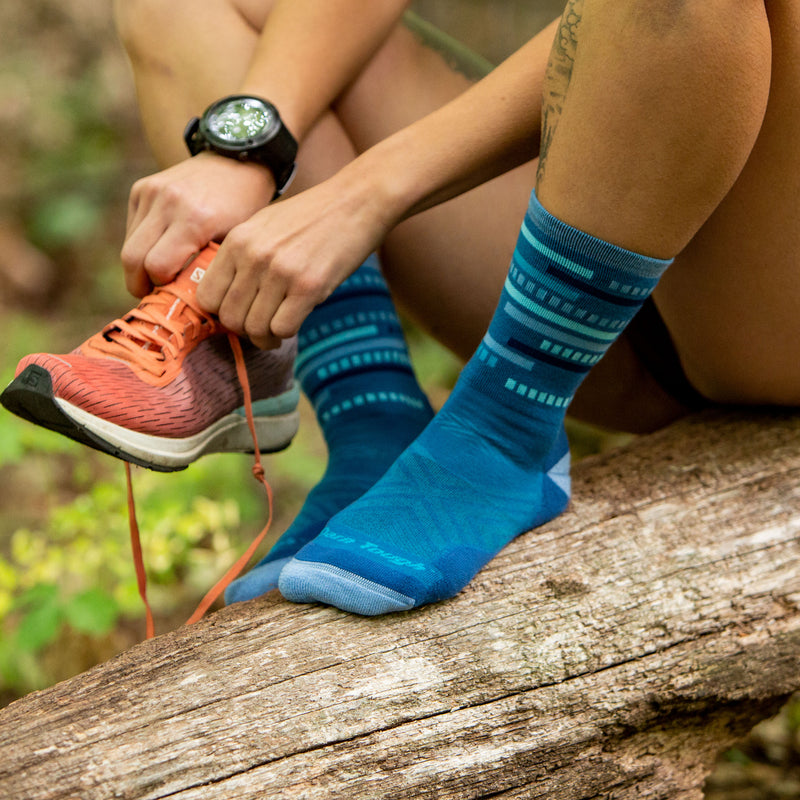 Close up of a woman's legs, while sitting on a log and putting on a running shoe, knees bent, wearing Women's Checkpoint Micro Crew Ultra-Lightweight Running Socks in Baltic, Lifestyle Image