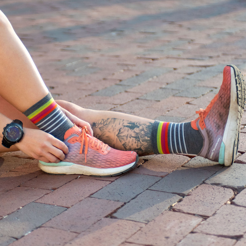 A woman sits on brick pavement wearing running shoes and Women's Stride Micro Crew Ultra-Lightweight Running Sock in Gray, Lifestyle Image
