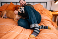 Lifestyle image of a man laying on his bed with his dog, wearing jeans and his Oxford Crew Lightweight Lifestyle Socks in Gray, Lifestyle Image