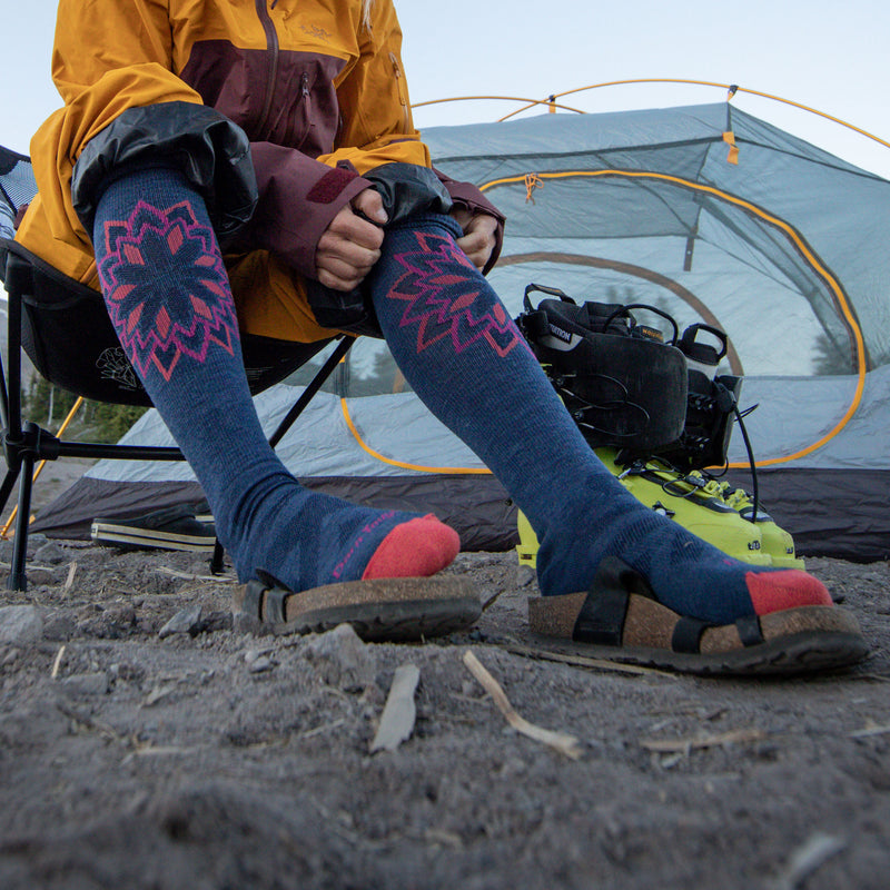 Image of a woman sitting outside of her tent, pulling up her Women's Sacred Over the Calf Midweight Ski & Snowboard Socks in Denim, Lifestyle Image