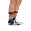 Profile image of woman's legs on a white background, facing right, wearing Women's Starboard Crew Lightweight Lifestyle Socks in Navy with one foot in a casual sneaker