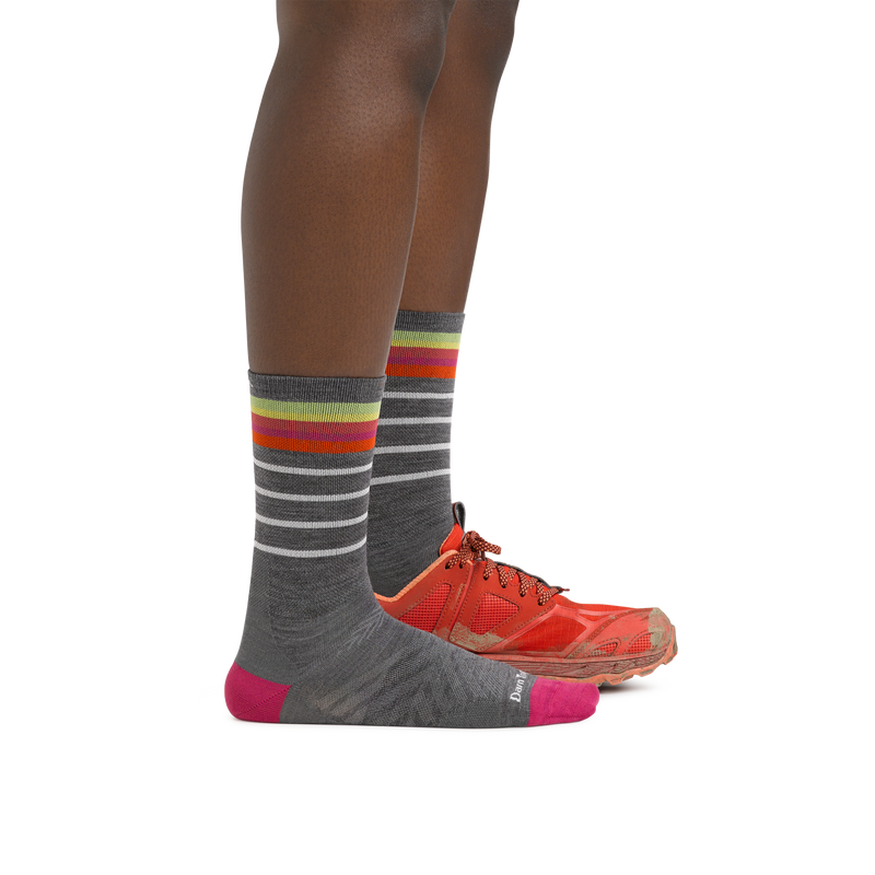 Profile image of a woman's legs on a white background wearing Women's Stride Micro Crew Ultra-Lightweight Running Sock in Gray with one foot also in a running shoe
