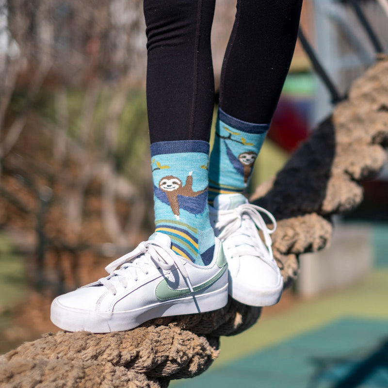 Close up shot of a girl balancing n a large rope, wearing white sneakers and wearing Lazy Daze Micro Crew Hiking sock in aqua, Lifestyle Image