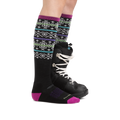 Profile image of a woman's legs on a white background wearing Women's Northstar Over the Calf Midweight Ski & Snowboard Socks in Black with one foot also in a snowboard boot