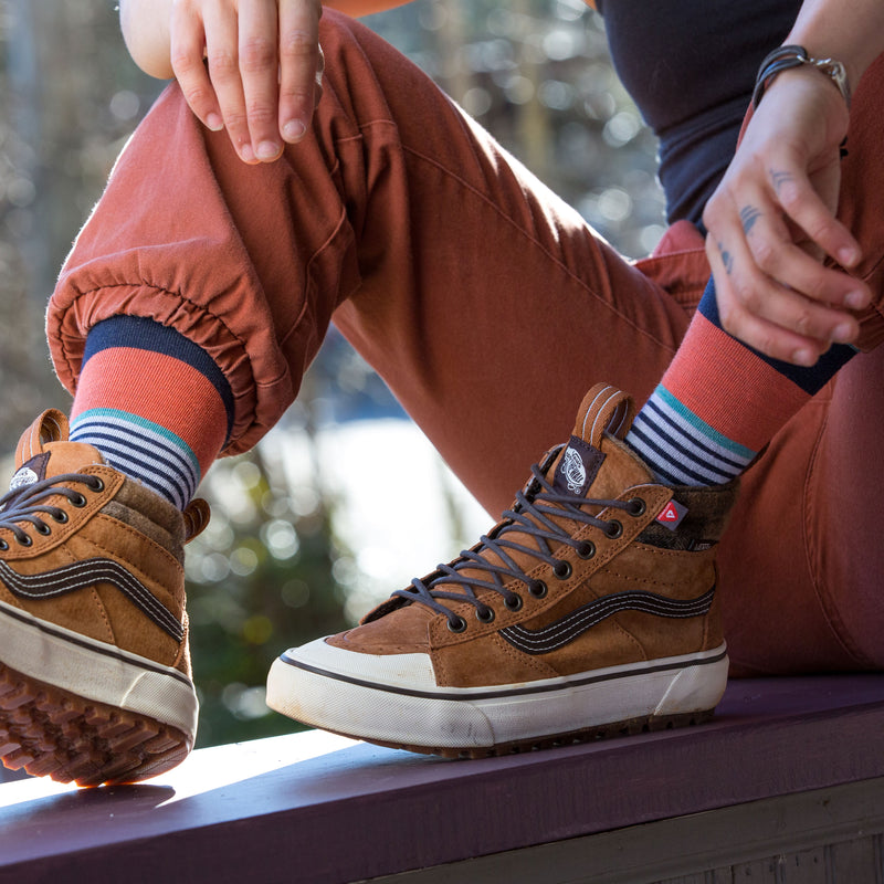 Woman sitting down, wearing salmon colored pants and brown shoes with the starboard lifestyle socks in navy, Lifestyle Image