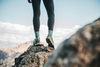 Waist down image of a woman's legs, standing on a rocky mountaintop, wearing Women's Hiker Micro Crew Midweight Hiking Socks in Aqua Heather, Lifestyle Image