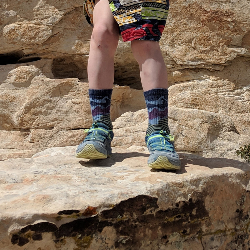 Kid standing on a rocky ledge, wearing hiking shoes and shorts wearing Three Peaks Micro Crew Hiking Sock in Denim, Lifestyle Image