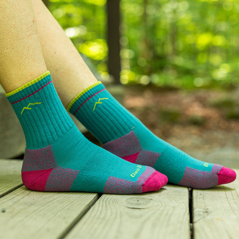 Close up image of a woman's feet on a wooden porch in the woods wearing Coolmax Hiker Micro Crew Midweight Hiking Socks in Teal, Lifestyle Image