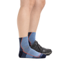 Profile image of a woman's legs on a white background, facing right, wearing Women's Hiker Quarter Midweight Hiking Socks in Denim Heather and a hiking shoe on one foot