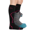 Profile image of a woman's legs wearing Women's Thermolite Over the Calf Midweight Ski & Snowboard Socks in Black/Boysenberry with a snowboard boot on one foot
