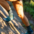 Woman climbing a rock, no shoes on, wearing stripes micro crew midweight hiking sock in aqua stripe, Lifestyle Image