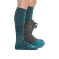 Profile image of a woman's legs facing to the right, wearing Women's Sea to Sky Over the Calf Lightweight Ski & Snowboard Socks in Teal with one foot also in a snowboard boot