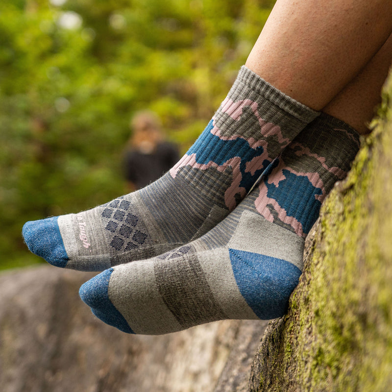 Close up image of a woman's feet, hanging off a rocky outcropping covered in moss wearing Women's Three Peaks Micro Crew Lightweight Hiking Sock in Light Gray, Lifestyle Image