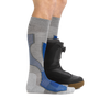 Man standing with feet facing right wearing Outer Limits Over the Calf Lightweight Ski & Snowboard Socks in Gray with back foot also wearing a black snowboard boot