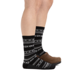 Profile image of a woman's legs on a white background, facing to the right, wearing Women's Bronwyn Crew Lightweight Lifestyle socks in Black with back foot also in a clog