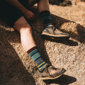 Close up lifestyle image of a man, sitting on a rock, wearing hiking boots and Unstandard Stripe Crew Lightweight Lifestyle Sock in Denim, Lifestyle Image