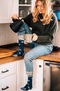 Woman sitting on a kitchen counter holding a mug, pouring herself a cup of hot water, wearing a sweater, jeans and Women's Umbrellas Crew Lightweight Lifestyle Sock in Denim, Lifestyle Image