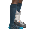 Profile image of a woman's legs, facing right, wearing Women's RFL Over the Calf Ultra-Lightweight Ski & Snowboard Socks in Dark Teal with one foot also in a ski boot