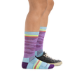 Profile image of a woman's legs on a white background wearing Women's Waves Crew Lightweight Lifestyle Sock in Purple with one foot in a casual shoe