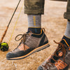 Close up Lifestyle Image of a man sitting with feet swinging wearing sneakers and Retro Crew Lightweight Lifestyle Socks in Gray