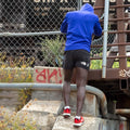 Image of a runner leaning against a chain link fence, stretching, wearing Men's Run No Show Running socks in White, Lifestyle Image