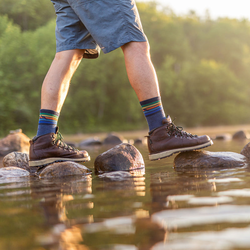 Lifestyle image of man stepping over rocks in a stream wearing shorts, hiking boots and Kelso Micro Crew Lightweight Hiking Sock in Denim, Lifestyle Image