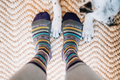 Perspective image of looking down at a woman's feet, standing on a cream rug with a dogs paws next to her feet wearing Women's Bronwyn Crew Lightweight Lifestyle Socks in Taupe, Lifestyle Image