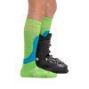 Profile image of kid legs facing to the right wearing Fall Line Over the Calf Lightweight Ski & Snowboard Socks in Green with rear foot also in a ski boot