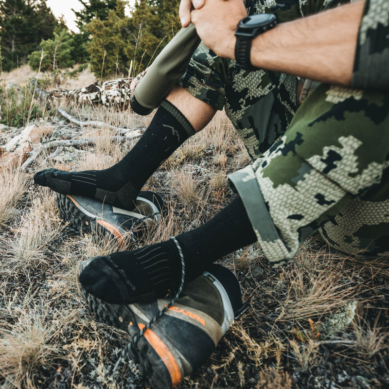 A hunter sitting on the ground with his feet resting on his boots wearing darn tough socks for hunting, Lifestyle Image