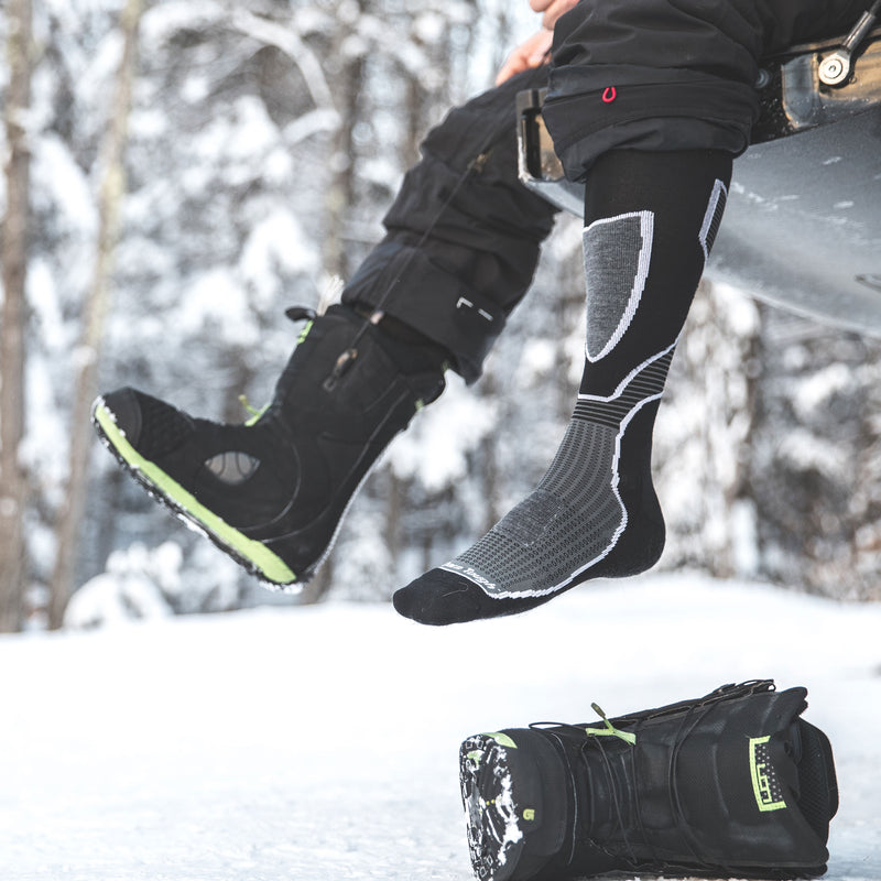 Close up lifestyle image of a man sitting on a tailgate swinging his feet, one foot wearing a snowboard boot and the other foot wearing Outer Limits Over the Calf Lightweight Ski & Snowboard Socks in Black with the snowboard boot on the ground, Lifestyle Image