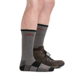 Man standing facing right, front foot barefoot wearing Coolmax Hiker Boot Hiking sock in gray/black and back foot wearing the sock and a hiking boot