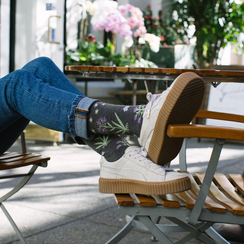 Image of a woman sitting in a chair outside, legs outstretched with feet resting on the arm of another chair, wearing jeans, white sneakers and Women's Folktale Crew Lightweight Lifestyle Socks in Taupe, Lifestyle Image