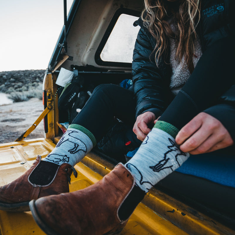 Woman sitting on a tailgate, pulling up Women's Woodland Creatures Lightweight Lifestyle Socks in Ash while wearing boots, Lifestyle Image