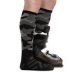 Profile image of Camo Over the Calf Midweight Ski & Snowboard socks in black facing the right with the back foot also in a snowboard boot