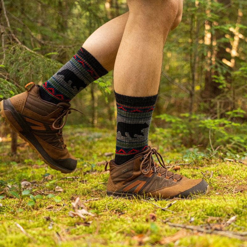 Close up lifestyle image of a man walking on a mossy trail in a forest, wearing hiking boots and VanGrizzle Boot Midweight Hiking Sock in Charcoal, Lifestyle Image