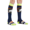 Kid standing barefoot on a white background wearing Kids Powderhound Over the Calf Midweight Ski & Snowboard Sock in Eclipse