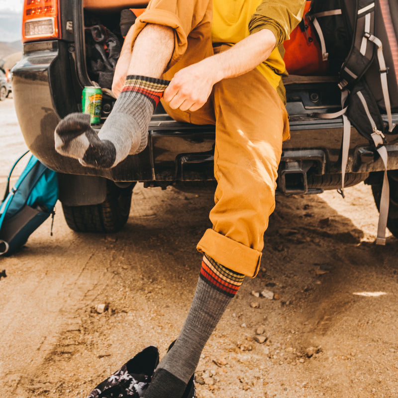 Lifestyle image of man sitting in the open back of his vehicle, pulling on his Kelso Micro Crew Lightweight Hiking Sock in Gray, Lifestyle Image