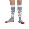 Image of a woman's legs on a white background, toes pointed out so that the gondola and the yeti in mountains are visible on Women's Yeti Over the Calf Ski & Snowboard Socks in Glacier