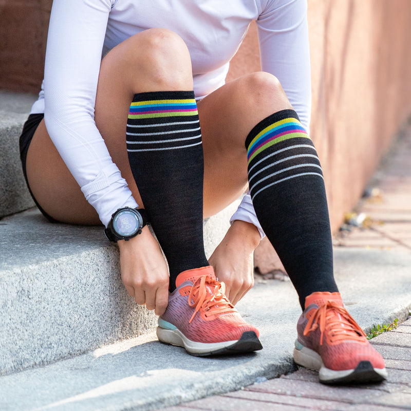 A woman sits on a curb fixing her running shoe wearing Women's Stride over the Calf Ultra-Lightweight Running Socks in Black, Lifestyle Image