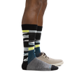 Profile of male legs facing to the right wearing Icefields Crew Lightweight Lifestyle Sock in Gray and a casual shoe on the foot in back