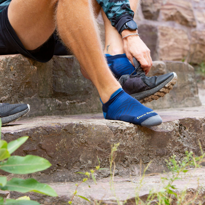Man sitting on stone steps putting on a running shoe wearing running shorts and Men's Run No Show Running Socks in Eclipse, Lifestyle Image