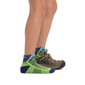 Profile image of kid legs facing to the right wearing Hiker Quarter Lightweight Hiking socks in Green with foot in rear also wearing a hiking boot