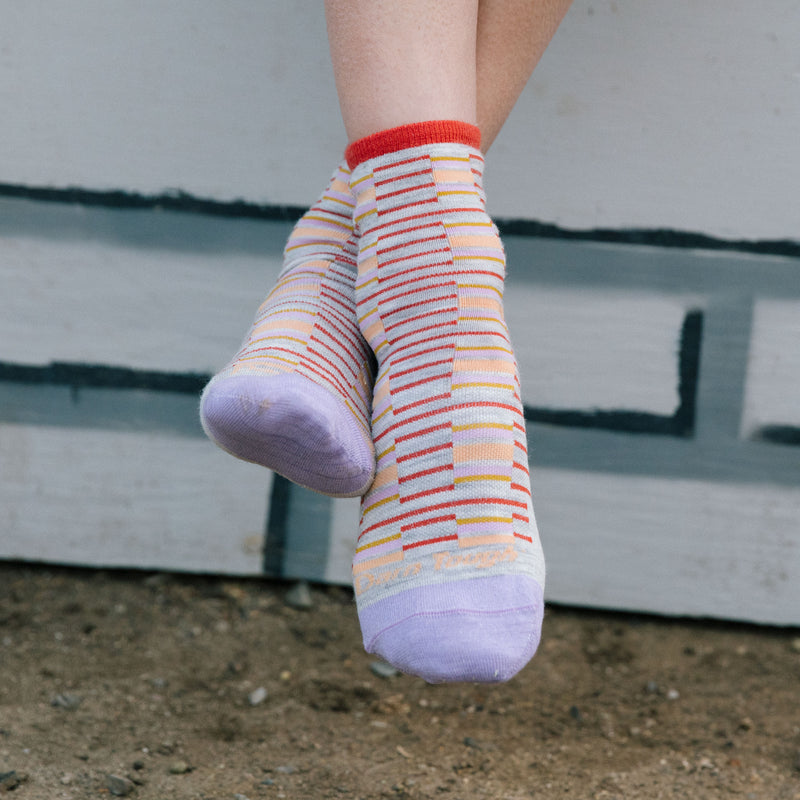 A women's feet crossed wearing darn tough picnic shorty casual socks in Ash with red and yellow stripes. Lifestyle Image