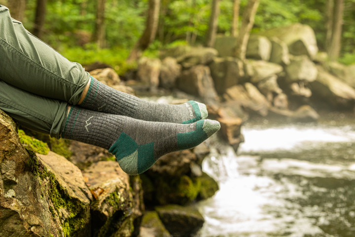 Image of a woman's legs, ankles crossed, hanging over a stream wearing Women's Hiker Micro Crew Midweight Hiking Socks in Slate, Lifestyle Image