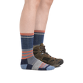 Profile image of a woman's legs on a white background, facing to the right, wearing Women's Her Spur Boot Lightweight Hiking Socks in Denim with one foot also in a hiking boot