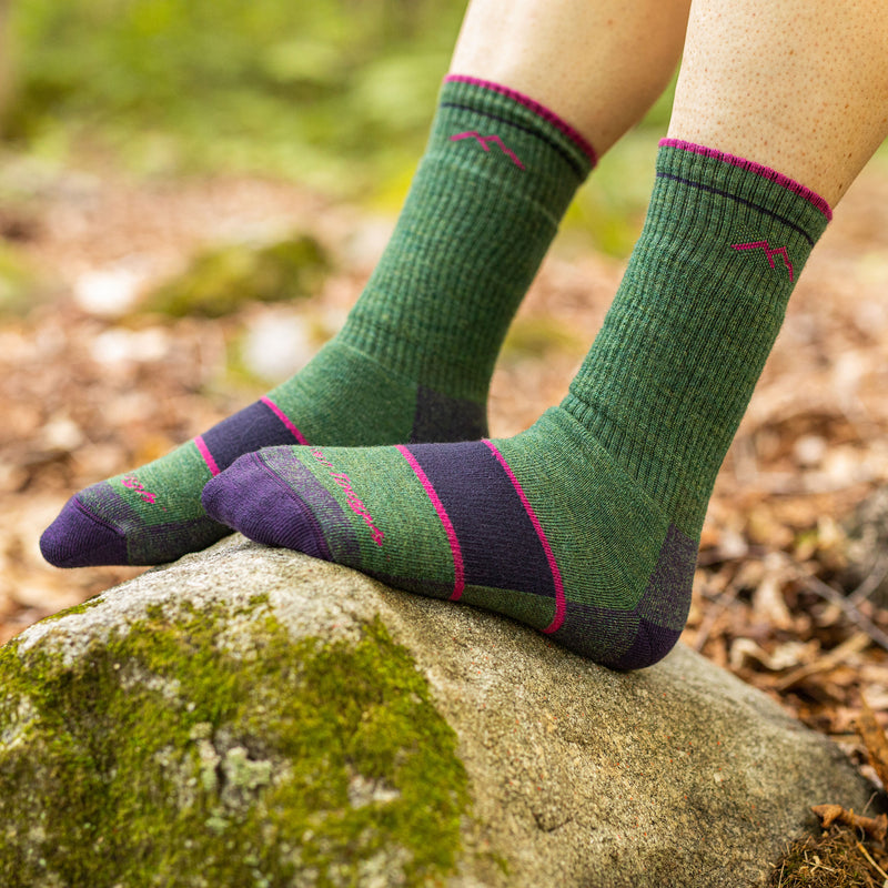 Close up of a woman resting her feet on a rock, barefoot, wearing Women's Hiker Boot Midweight Hiking Socks in Moss, Lifestyle Image