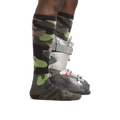 Profile image of a woman's legs on a white background wearing Women's Camo Over the Calf Midweight Ski & Snowboard socks in Forest with one foot also in a ski boot