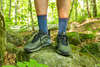 Closeup Lifestyle Image of man wearing darn tough light hiker micro crew hiking socks with hike shoes standing on a rock in the woods
